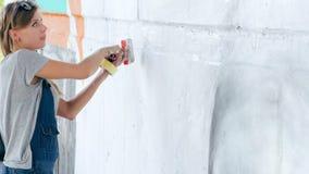 Het gezicht van Drawing van de graffitikunstenaar van mooie vrouw met verf op Straatmuur Wijfje die met borstel werken Stedelijk  stock footage
