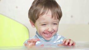 Het gezicht van een gelukkig die kind, met een viltpen wordt bevlekt Een vuile kindlach en spelen Het kind is bevlekt met verven stock footage