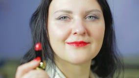 Het gezicht van een glimlachende vrouw met heldere rode lippenstift op haar lippen houdt lippenstift in haar hand Close-up De nad stock footage