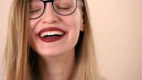 Het gezicht van een jonge emotionele gelukkige vrouw met lange blondehaar en glazen Gelukkig lach, die de camera bekijken stock footage