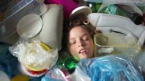 Het gezicht van een kind in een stapel van plastic afval Plastic verontreiniging van de planeet Sparen de aarde stock videobeelden