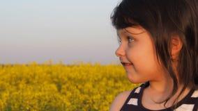 Het gezicht van een klein meisje in aard Het gezicht van het kind is close-up Het kind is in gele bloemen Koolzaad, Canola, Biodi stock footage