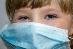 Het gezicht van een klein meisje in een medisch masker bescherming tegen virussen royalty-vrije stock foto's