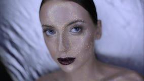 Het gezicht van het meisje is behandeld met glans en schittert posing stock video