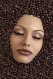 Het gezicht van het meisje dat in koffiebonen wordt ondergedompeld Stock Fotografie