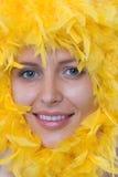 Het gezicht van het meisje in een frame van gele veren Stock Afbeelding