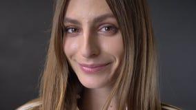 Het gezicht van jong charmant meisje let op bij camera, flirtconcept, grijze achtergrond stock video
