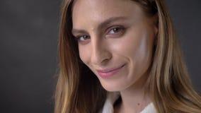 Het gezicht van jong charmant meisje let op bij camera, het knipogen, flirtconcept, grijze achtergrond stock videobeelden
