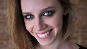 Het gezicht van jong charmant meisje met rokerige ogen let op bij camera, het glimlachen, vage achtergrond stock videobeelden