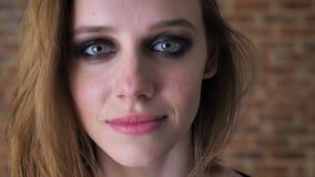 Het gezicht van jong charmant meisje met rokerige ogen let op bij camera, vage achtergrond stock videobeelden