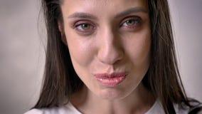 Het gezicht van jong donkerbruin meisje let op bij camera, het lachen, grijze achtergrond stock videobeelden