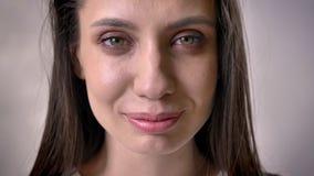 Het gezicht van jong donkerbruin meisje let op bij camera, open ogen, grijze achtergrond stock footage