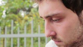 Het gezicht van jong gebaard donker haired mannetje met bruine ogen concentreerde zich op iets stock video