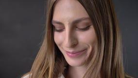 Het gezicht van jong schuw meisje let op bij camera, het glimlachen, grijze achtergrond stock video