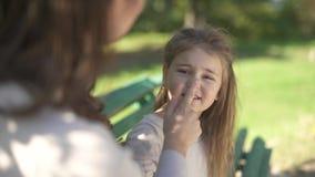 Het gezicht van moederhuisdieren van haar dochter bij het park stock footage