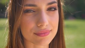 Het gezicht van sexy vrouw let op bij camera in park in dag, flirtconcept, vage achtergrond stock video