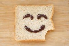 Het gezicht van Smiley op een stuk van zwart brood Stock Afbeeldingen