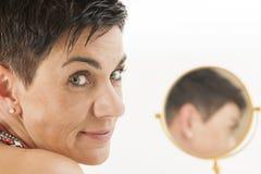 Het gezicht van vrouw onderzoekt de camera met spiegel Royalty-vrije Stock Foto