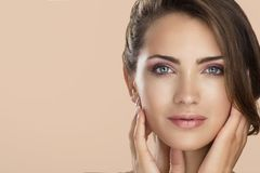 Het gezichtsportret van de vrouwenschoonheid op neutrale kleur met stock afbeelding