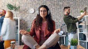 Het gezoem uit dame die aan muziek het ontspannen in bureau op lijst in lotusbloem luisteren stelt stock footage