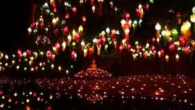 Het gezoem van kaarslichten in het beeld van Boedha stock video