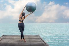 Het gezonde de bal van de vrouwenlevensstijl evenwichtige yoga praktizeren mediteert en energie op de brug in ochtend de kust stock foto