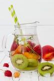 Het gezonde detoxfruit goot op smaak gebracht water De zomer die eigengemaakte cocktail met vruchten, thyme op houten lijst verfr Stock Fotografie