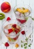 Het gezonde detoxfruit goot op smaak gebracht water De zomer die eigengemaakte cocktail met vruchten, thyme op houten lijst verfr Royalty-vrije Stock Afbeelding