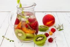 Het gezonde detoxfruit goot op smaak gebracht water De zomer die eigengemaakte cocktail met vruchten, thyme op houten lijst verfr Stock Foto