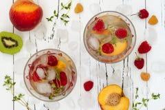 Het gezonde detoxfruit goot op smaak gebracht water De zomer die eigengemaakte cocktail met vruchten, thyme op houten lijst verfr Royalty-vrije Stock Afbeeldingen