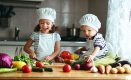 Het gezonde Eten De gelukkige kinderen bereidt plantaardige salade in kitc voor Stock Foto's