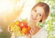 Het gezonde Eten een vrouw met een plaat van fruit in de zomer op natur Stock Afbeeldingen