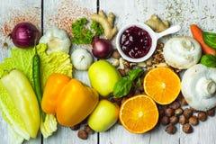 Het gezonde eten - kleurrijke, gezonde kruiden, kruiden, vruchten en groenten op witte houten lijst stock afbeelding