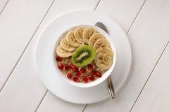 Het gezonde eten met havermeel in een kom op witte houten lijst Stock Fotografie