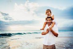 Het gezonde houdende van vader en dochter spelen samen bij het strand Stock Afbeelding