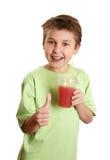 Het gezonde jongen het drinken sap beduimelt omhoog stock afbeelding