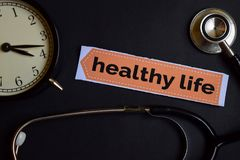 Het gezonde Leven op het drukdocument met de Inspiratie van het Gezondheidszorgconcept wekker, Zwarte stethoscoop royalty-vrije stock afbeeldingen