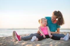 Het gezonde moeder en babymeisje uitrekken zich op strand Stock Afbeeldingen
