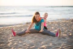 Het gezonde moeder en babymeisje uitrekken zich op strand Stock Fotografie
