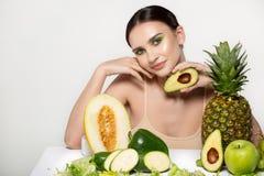 Het gezonde mooie donkerbruine meisje glimlachen, die de camera met avocado in hand dichtbijgelegen gezicht bekijken, die in de s stock afbeelding