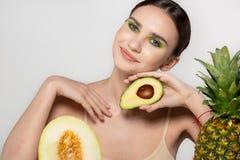 Het gezonde mooie donkerbruine meisje glimlachen, die de camera met avocado in hand dichtbijgelegen gezicht bekijken, die in de s stock fotografie