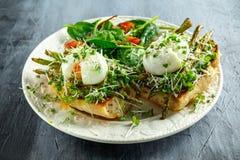 Het gezonde Ontbijt brak Avocado, asperge en stroopte ei op geroosterde die toosts voor ontbijt met salade en pruim wordt gediend stock foto