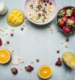 Het gezonde ontbijt met havermoutpap, de aardbeien, het verse jus d'orange, de mango en de noten plaatsen tekst, kader op houten  Royalty-vrije Stock Foto