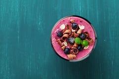 Het gezonde ontbijt van smoothie, dessert, yoghurt of milkshake met bevroren bosbes en haver verfraaide geraspte chocolade en mun Royalty-vrije Stock Fotografie
