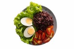 Het gezonde voedsel, schoon voedsel dat ongepelde rijst bevat, rijst, tomaten, kookte eieren, en groene bladsla in een schotel op stock afbeelding