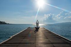 Het gezonde vrouwenlevensstijl essentieel uitoefenen mediteren en het praktizeren de yoga bij op de brugkust, aardachtergrond stock foto