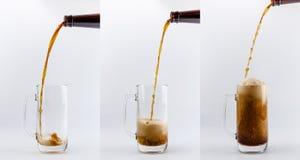 Het gieten proces van donker stoutbier in een mok, de plonsen, de dalingen en het schuim van het bierglas rond glas Stock Fotografie