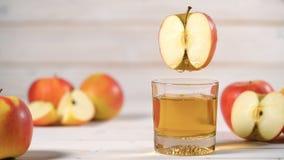 Het gieten van het appelsap in een glas van de besnoeiing van een appel, cinemagraph stock footage
