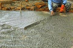 Het gieten van concrete mengeling voor wegenbouwarbeiders. Stock Afbeeldingen