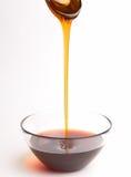 Het gieten van de honing van de lepel Stock Afbeeldingen